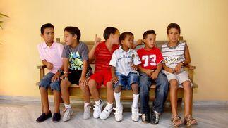 Un grupo de chicos posan sentados en un banco.  Foto: Manu Garc?