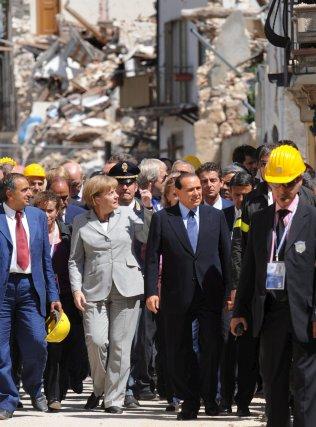 Berlusconi  y  Angela Merkel  recorren el pueblo de Onna, para comprobar los daños provocados por el terremoto del pasado de abril.  Foto: EFE