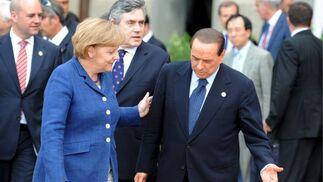 Berlusconi cede el paso a la canciller alemana Angela Merkel, para la tradicional foto de familia.  Foto: EFE