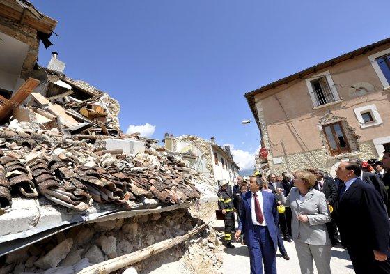 Merkel y Berlusconi visitan una de las zonas más afectadas por el terremoto de L'Aquila en Onna.  Foto: EFE