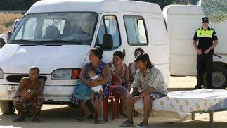 Una familia aguarda el momento de la marcha sentados en un colchón en plena calle mientras un agente de Policía les observa.  Foto: Juan Carlos  Vázquez/Juan Carlos Muñoz