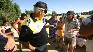 Un agente de la Policía Local trata de mediar con algunos chabolistas ante la orden de desalojo de Tablada.  Foto: Juan Carlos  Vázquez/Juan Carlos Muñoz