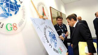 Sarkozy firma sobre el logo de la cumbre del G8.  Foto: EFE