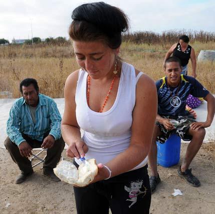 Yna joven se prepara un bocadillo ante la atenta mirada de algunos familiares.  Foto: Juan Carlos  Vázquez/Juan Carlos Muñoz