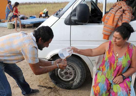 Una señora da agua a otro hombre en plena calle.  Foto: Juan Carlos  Vázquez/Juan Carlos Muñoz