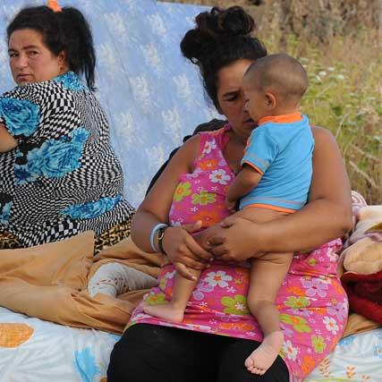 Un menor semi desnudo arropado por un familiar.  Foto: Juan Carlos  Vázquez/Juan Carlos Muñoz