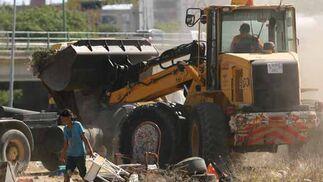 Una máquina recoge la basura acumulada en el poblado mientras una menor sigue recopilando pertenencias.  Foto: Juan Carlos  Vázquez/Juan Carlos Muñoz