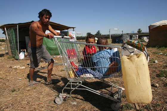 Un hombra utiliza un carro de la compra para trasnportar a sus dos menores y algunos enseres.  Foto: Juan Carlos  Vázquez/Juan Carlos Muñoz