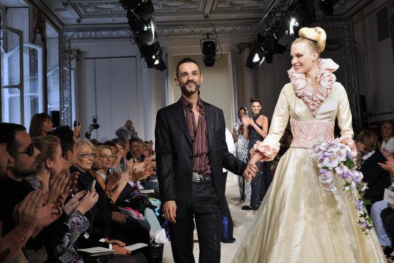El diseñador franco-eslavo Oliver Swan agradece al público junto a una modelo.  Foto: EFE