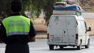 Una furgoneta cargada de enseres personales abandona la carretera de El Copero ante la mirada de un agente de Policía.  Foto: Juan carlos Vázquez