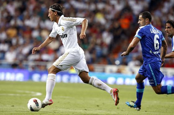Özil conduce una pelota perseguido por un rival. / EFE