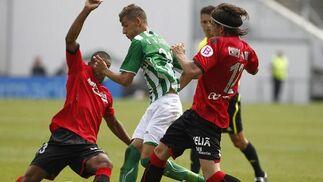 Vadillo trata de sortear a dos jugadores del Mallorca. / Antonio Pizarro