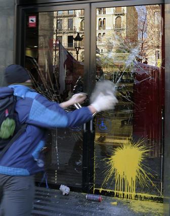 Un joven lanza piedras y bolas de pintura contra un banco.  Foto: AFP Photo