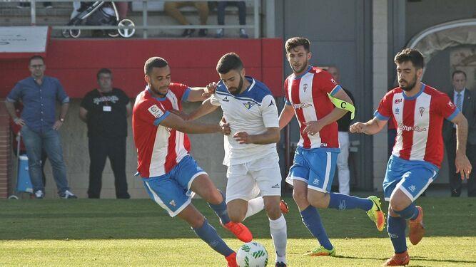 Manu Reina conduce la pelota ante la presión de Pablo Ganet e Iván Turrillo y Tano siguen la jugada.