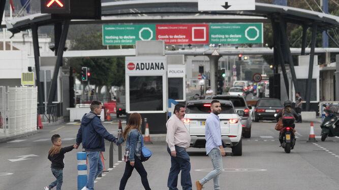 Un grupo de personas pasan frente a la aduana de La Línea.