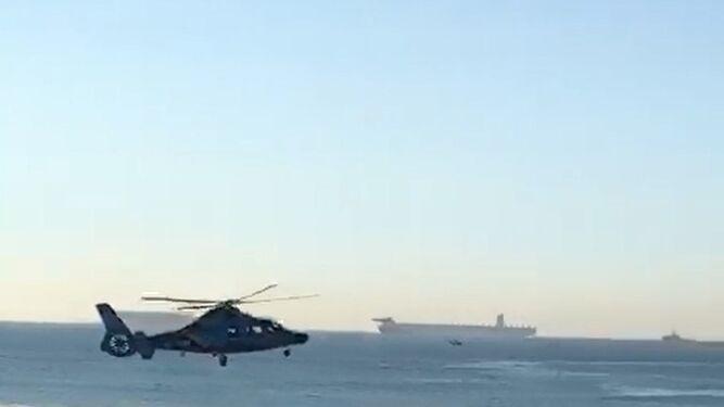 Capturas del vídeo con el helicóptero sobre la embarcación y sus tripulantes huyendo.