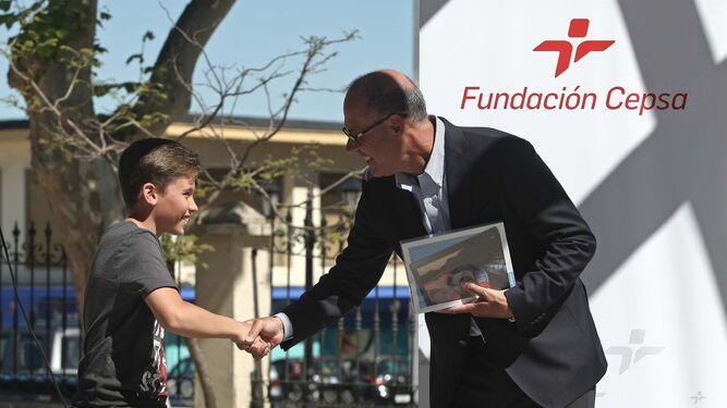 Pérez de la Blanca felicita a uno de los niños al entregarle el premio.