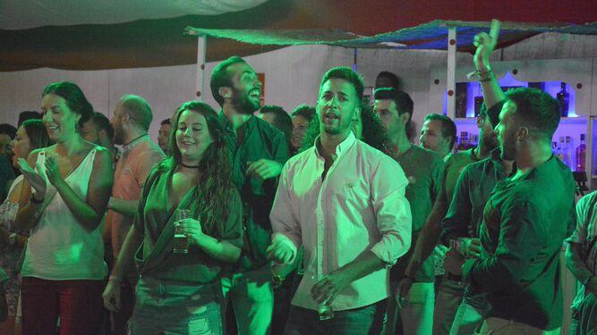 Un grupo de jóvenes baila y se divierte en una de las casetas.
