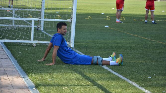 El jugador albirrojo Ernesto García, con una férula en la rodilla derecha, observa un entrenamiento del equipo.