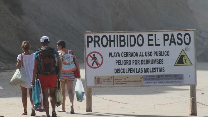 Tres bañistas acceden a una de las zonas prohibidas haciendo caso omiso al cartel de advertencia que tienen al lado.