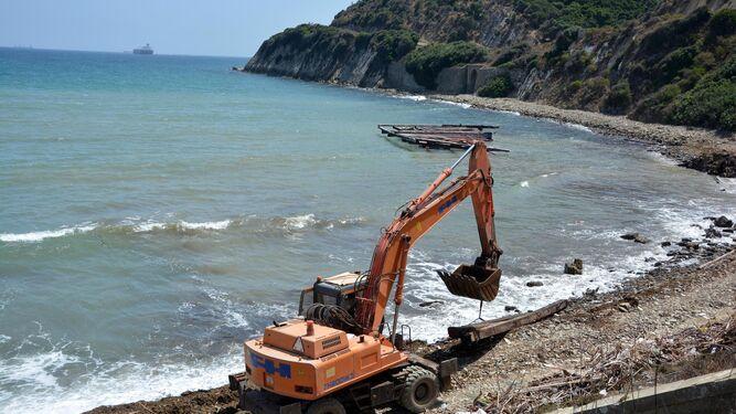 Una máquina, en plena orilla de la cala entre la madera desguazada y una batea al fondo, ayer.