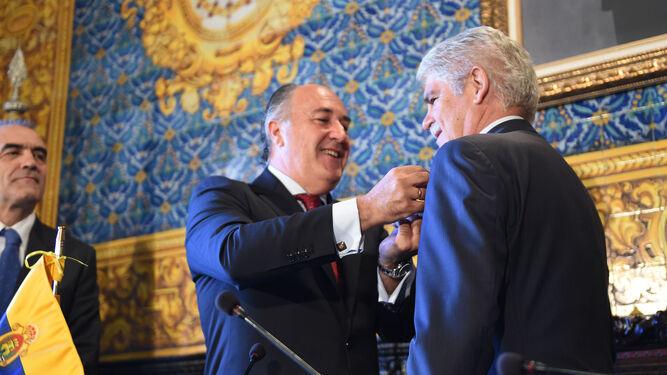 Dastis se dispone a firmar en el libro de honor de La Línea, ojeado por el alcalde, Juan Franco.