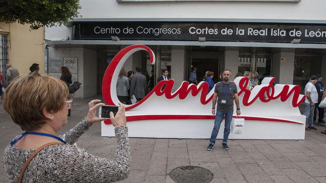 Uno de los asistentes al Congreso Leyenda Camarón posa ante el letrero con el nombre del cantaor que se ha hecho por el 25 aniversario.