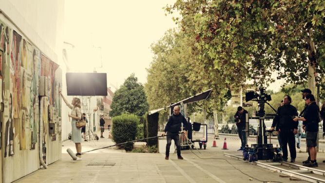El director Jota Linares, con Natalia de Molina. Abajo, un momento del rodaje en Sevilla.