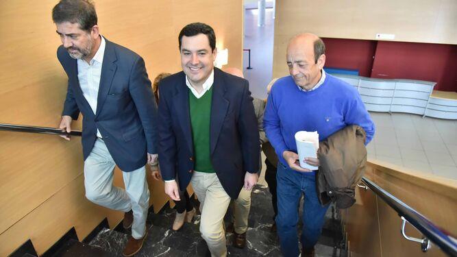 Juanma Moreno, en el centro y con Pablo Arriaga a su izquierda, a su llegada al Palacio de Congresos de La Línea, ayer.