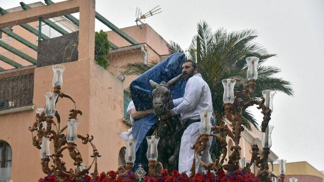 Hermanos de la Borriquita tapan la imagen del Señor para protegerlo de la lluvia.