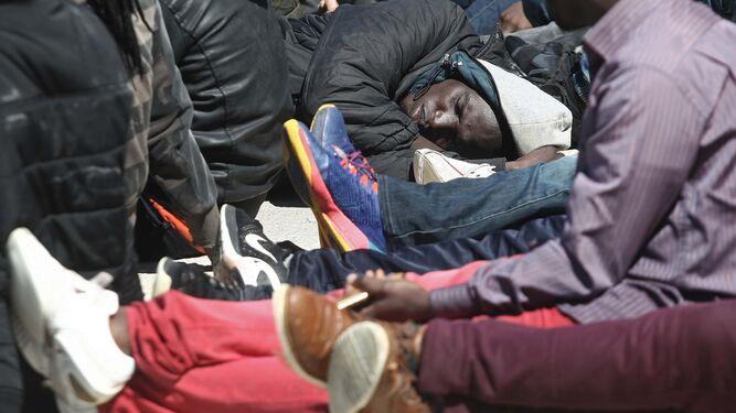 Un hombre descansa a su llegada al Puerto de Tarifa.