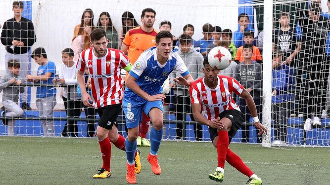 Pablo de Castro saca el balón, en presencia de Iván y de un contrario.