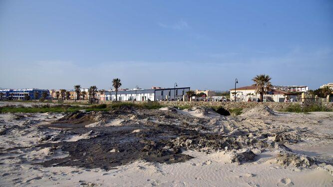 Los restos de lodo mezclados con fecales puestos a secar sobre la arena de Los Lances, ayer por la tarde.