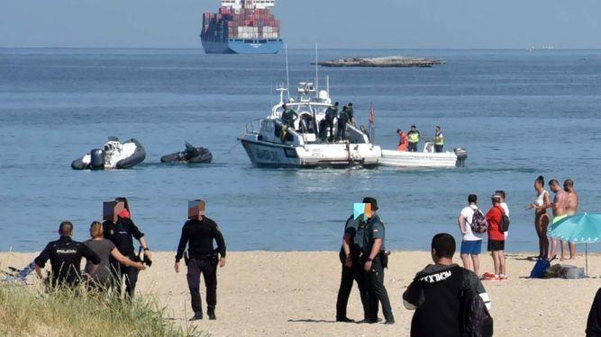 Policía Nacional y Guardia Civil trabajan en la playa. Al fondo, las embarcaciones implicadas en los hechos