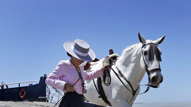 Una peregrina desembarcando con su caballo en Doñana.