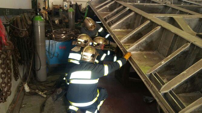 Los bomberos miran bajo la estructura a su llegada a la nave.