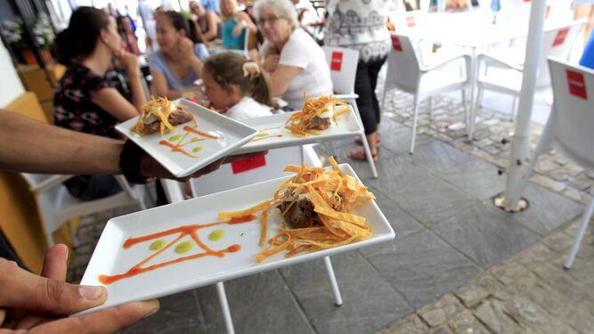 Un camarero se dispone a servir tapas en un restaurante de Tarifa